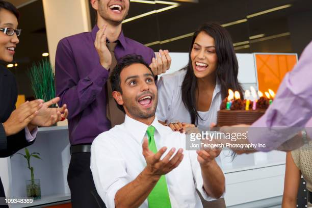 Hispanic co-workers surprising businessman with birthday cake