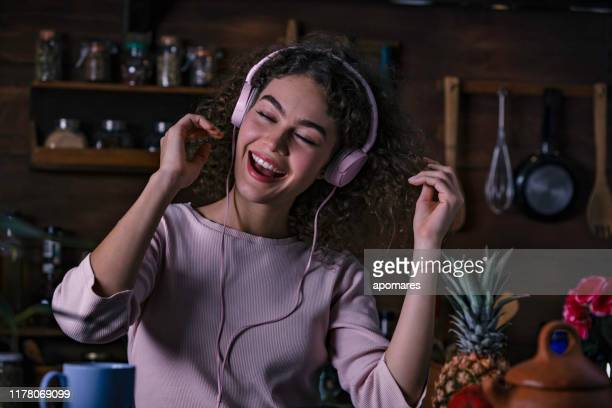 adolescente do cabelo curly latino-americano que escuta a música no telefone esperto na baixa cozinha rústica chave - rústico - fotografias e filmes do acervo