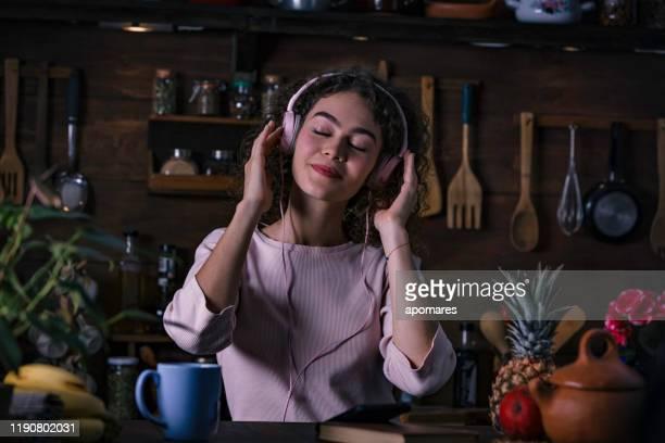 低キー素朴なキッチンでスマートフォンで音楽を聴くヒスパニック巻き髪十代の女の子 - ローキー ストックフォトと画像