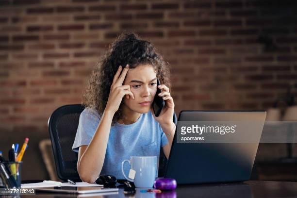 hispanic curly hair worried young woman using laptop and using mobile phone working at home office - banging your head against a wall stock pictures, royalty-free photos & images