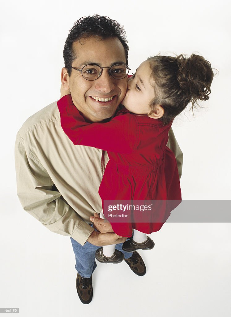 hispanic dad holds a young daughter in red dress who kisses his cheek : Foto de stock