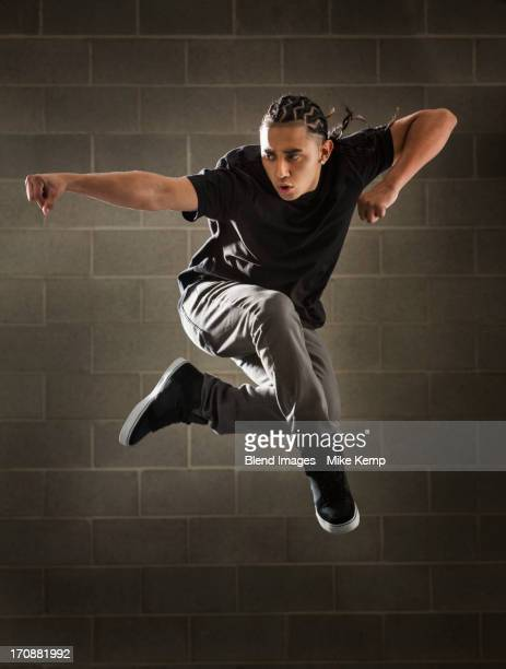 Hispanic dancer leaping in mid air