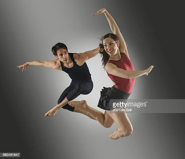 Hispanic dancers leaping in mid-air