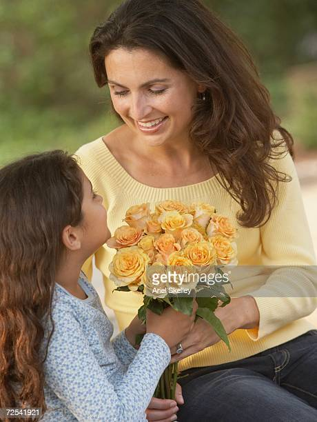 Hispanic daughter giving mother flowers