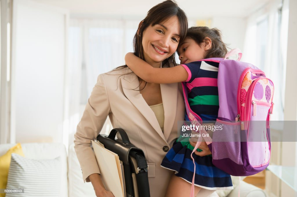 Hispanic daughter hugging mother as she leaves for work : Stock Photo