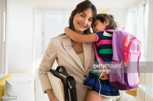 hispanic daughter hugging mother as she leaves for work - routine stock-fotos und bilder