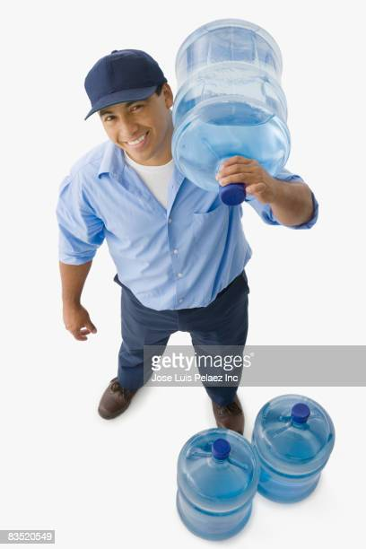 Hispanic delivery man delivering replacement water bottles