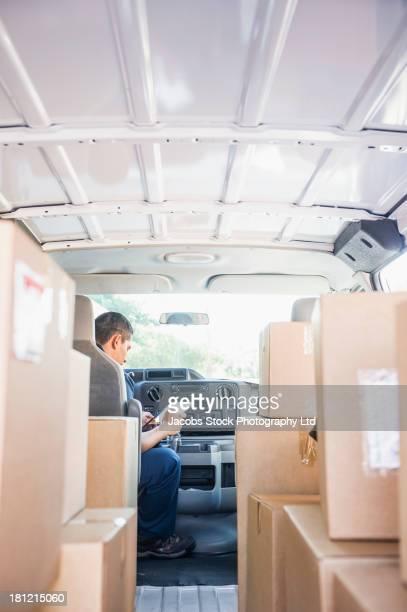 Hispanic deliveryman sitting in van