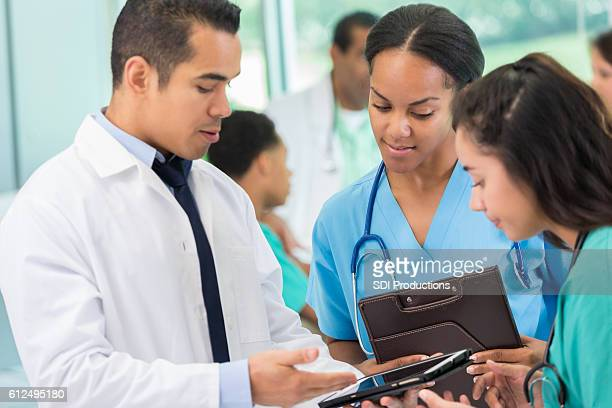 Hispanic doctor discusses patient with colleagues