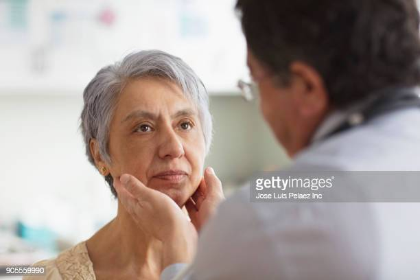 Hispanic doctor examining neck of patient