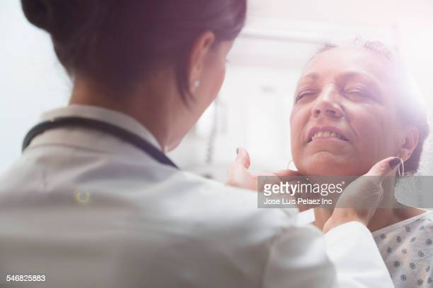 Hispanic doctor examining older patient
