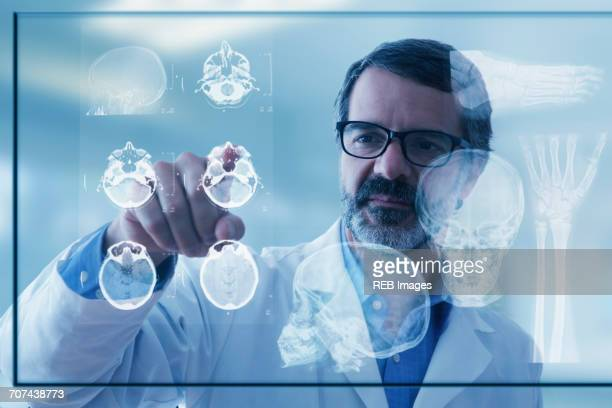hispanic doctor examining x-rays on virtual screen - realtà aumentata foto e immagini stock