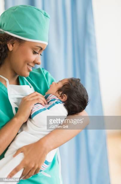 Hispanic doctor holding newborn in hospital