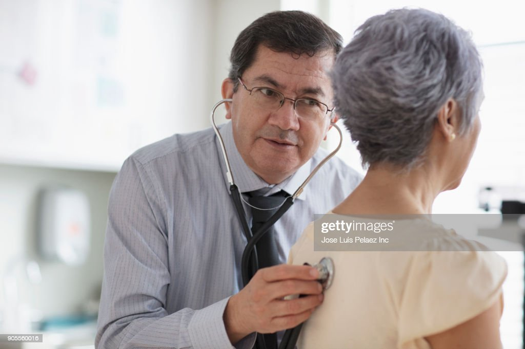 Hispanic doctor listening to back of patient with stethoscope : Stock Photo