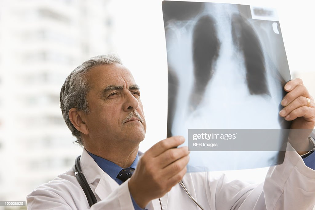 Hispanic doctor looking at x-ray : Stock Photo