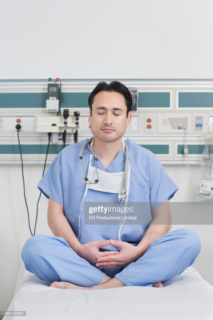 Hispanic doctor meditating on hospital bed : Stock Photo
