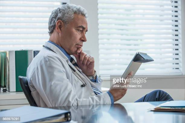 Hispanic doctor reading medical chart in office