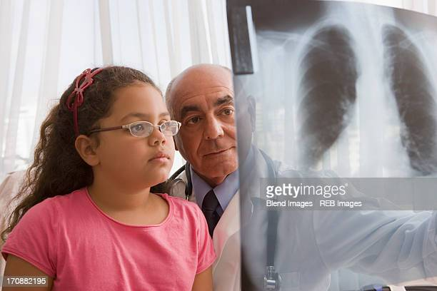 Hispanic doctor showing chest x-rays to patient