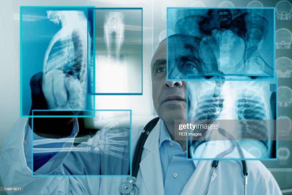 Hispanic doctor using virtual computer screen : Stock Photo