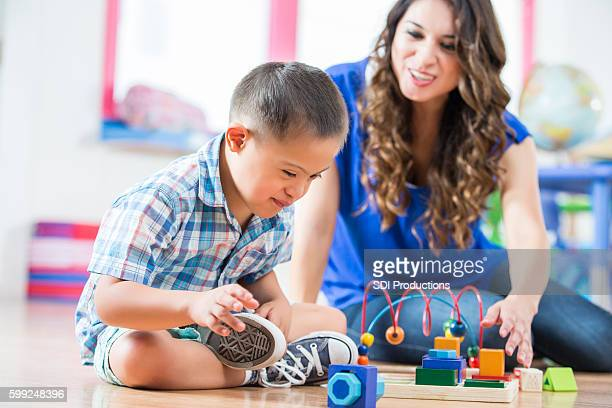 hispanic down syndrome boy reaching for toys at daycare center - down syndrome stock pictures, royalty-free photos & images