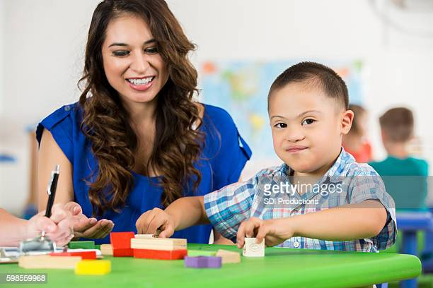 Hispanic Down Syndrome child playing with blocks at daycare