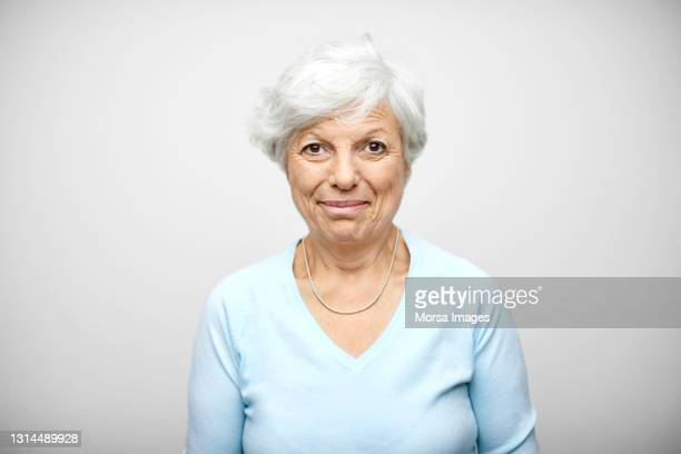 hispanic elderly woman against gray background - white hair stock pictures, royalty-free photos & images