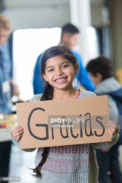 Hispanic elementary age girl holding GRACIAS sign in food bank