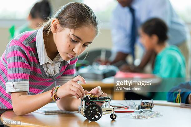 Hispanic elementary student building robot during science class