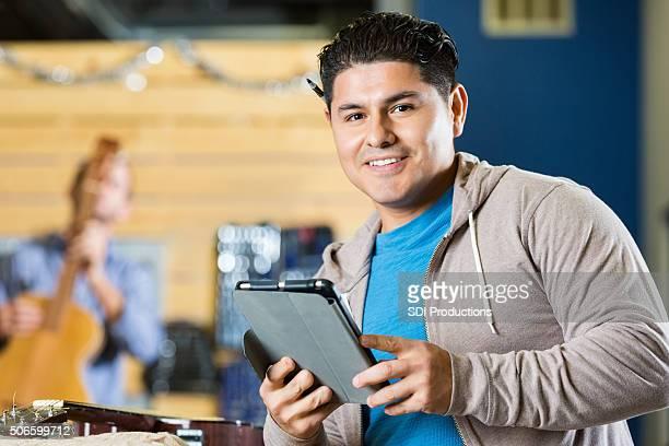 Hispanic Unternehmer Arbeiten in Musik instrument repair shop