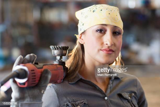 Hispanic factory worker holding metal fabricator