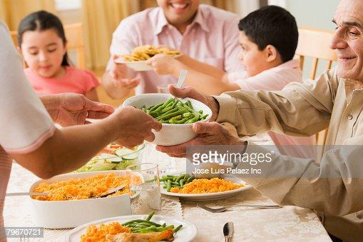 Hispanic Family Praying At Dinner Table Stock Photo