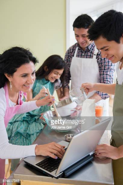 Hispanic family baking in kitchen