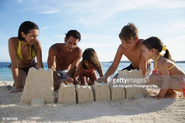 Hispanic family building sand castle