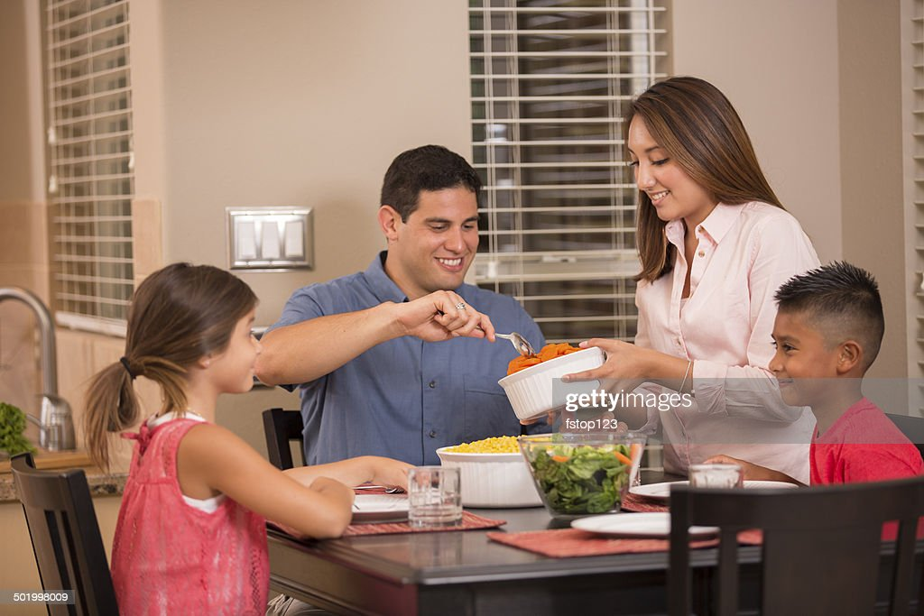 Hispanic Family Eating Dinner Together At Home Stock Photo