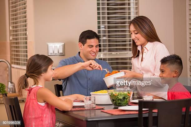 Hispanic Family Eating Dinner Together At Home