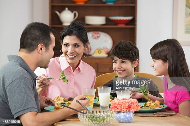 hispanic family eating dinner together - mom sits on sons lap stock pictures, royalty-free photos & images