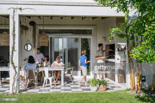 hispanic family enjoying outdoor midday meal - patio stock pictures, royalty-free photos & images