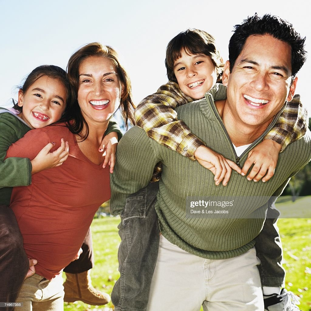 Hispanic Family Giving Piggy Back Rides In Park High-Res