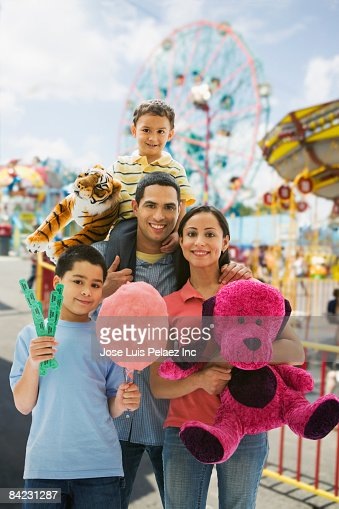 Hispanic Family Having Fun At Amusement Park Stock Photo