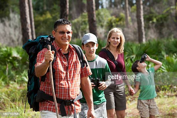 Hispanic family hiking in woods