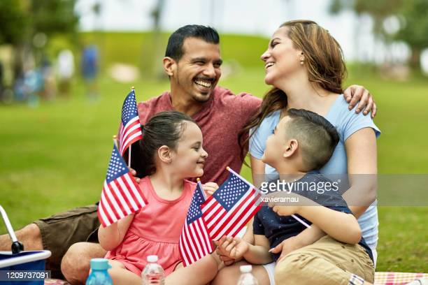 hispanic family holding american flags on holiday - celebration fl stock pictures, royalty-free photos & images