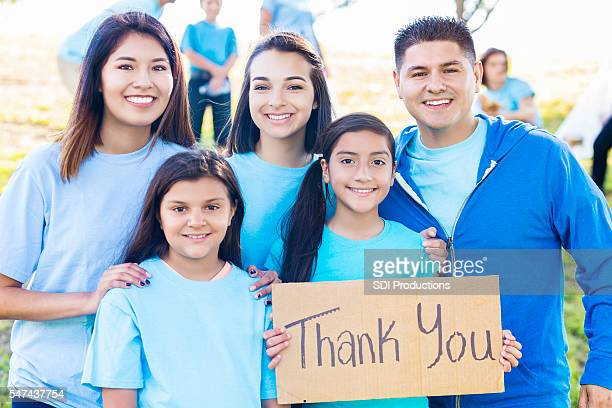 hispanic family holding 'thank you' sign during park beautification event - thank you phrase stock pictures, royalty-free photos & images
