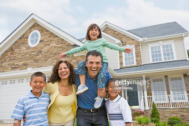 hispanic family in front of house - mortgage stock pictures, royalty-free photos & images
