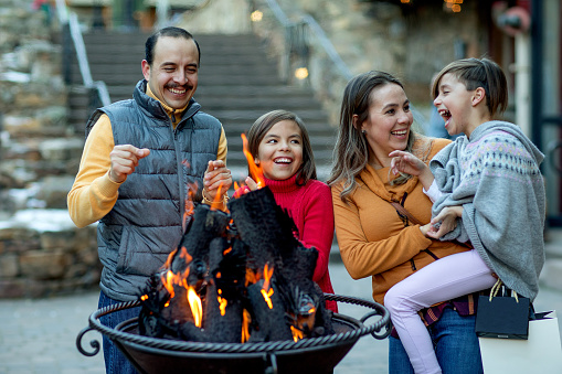 Hispanic family laughing around fire pit in a luxury mountain ski town. - gettyimageskorea