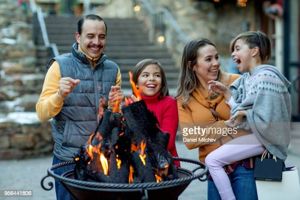 hispanic family laughing around fire pit in a luxury mountain ski town. - ski holiday stock pictures, royalty-free photos & images