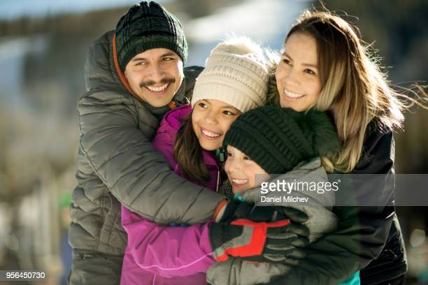 hispanic family of father, mother and two daughters hugging eachother, laughing and having fun at a ski resort. - purple glove stock pictures, royalty-free photos & images