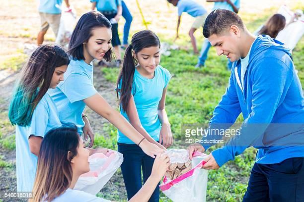 Hispanic family picking up trash in the park
