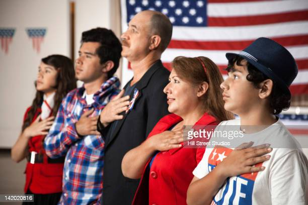 hispanic family pledging allegiance to the american flag - citizenship stock pictures, royalty-free photos & images