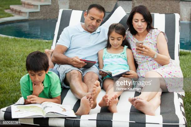 Hispanic family relaxing on deck chair in backyard