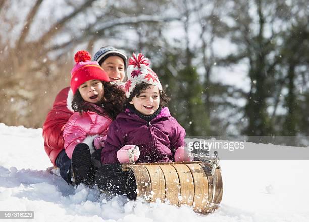 hispanic family sledding in snow - tobogganing stock pictures, royalty-free photos & images